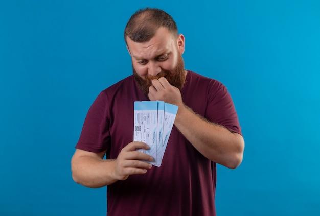Młody brodaty mężczyzna w brązowej koszulce trzymającej bilety lotnicze zestresowany i nerwowo obgryzający paznokcie