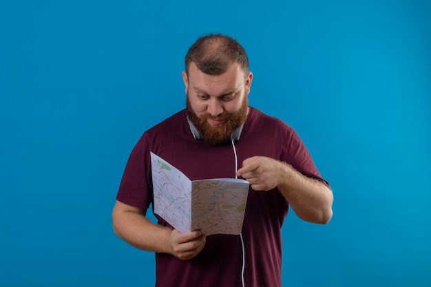 Młody brodaty mężczyzna w brązowej koszulce ze słuchawkami na szyi, trzymając mapę patrząc na nią, wskazując palcem z poważną miną