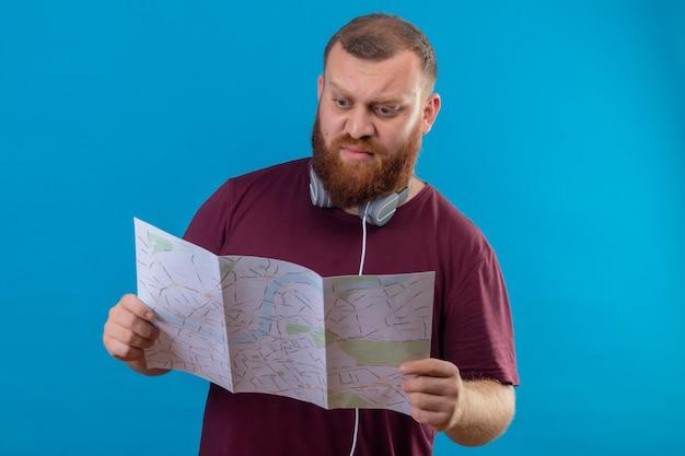 Młody brodaty mężczyzna w brązowej koszulce ze słuchawkami na szyi, trzymając mapę patrząc na nią zaskoczony