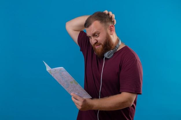 Młody brodaty mężczyzna w brązowej koszulce ze słuchawkami na szyi trzymający mapę, patrząc na nią zdziwiony