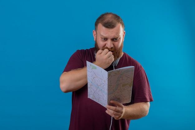 Młody brodaty mężczyzna w brązowej koszulce ze słuchawkami na szyi trzymający mapę patrząc na nią zestresowany i nerwowo obgryzający paznokcie