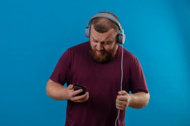 Młody brodaty mężczyzna w brązowej koszulce ze słuchawkami, trzymając telefon komórkowy, szukając ulubionej piosenki