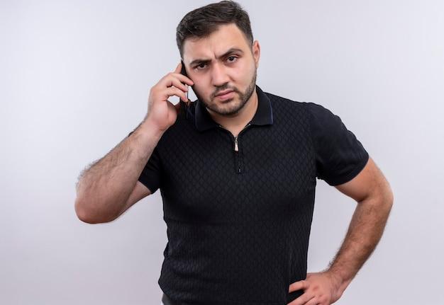 Młody brodaty mężczyzna w czarnej koszuli rozmawia przez telefon komórkowy z gniewną twarzą