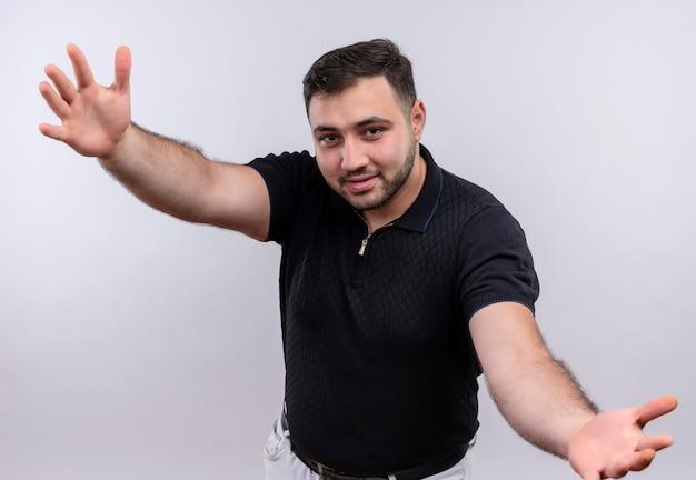 Młody brodaty mężczyzna w czarnej koszuli szeroko otwierające ręce robi powitalny gest