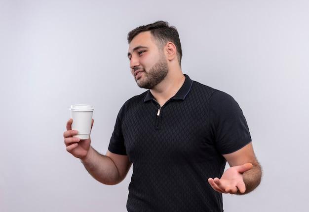 Młody brodaty mężczyzna w czarnej koszuli trzyma filiżankę kawy patrząc na bok gestykuluje ręką