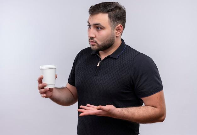 Młody brodaty mężczyzna w czarnej koszuli trzyma filiżankę kawy patrząc na bok niezadowolony gestykuluje ręką