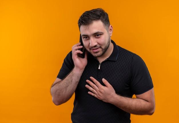 Młody brodaty mężczyzna w czarnej koszuli uśmiecha się podczas rozmowy przez telefon komórkowy