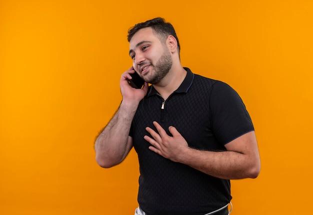 Młody brodaty mężczyzna w czarnej koszuli uśmiechnięty szczęśliwy i pozytywny podczas rozmowy przez telefon komórkowy