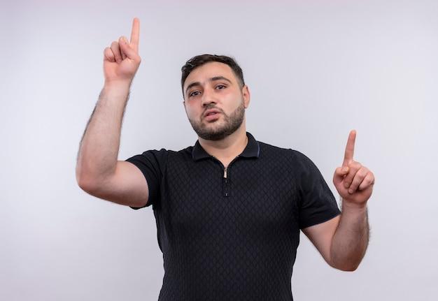Młody brodaty mężczyzna w czarnej koszuli, wskazując palcami wskazującymi z pewną poważną miną