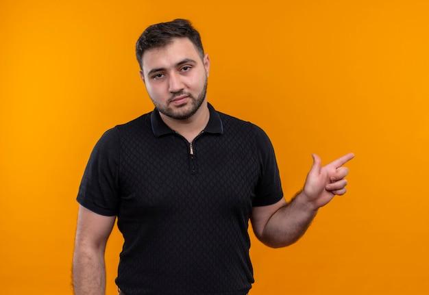 Młody brodaty mężczyzna w czarnej koszuli, wskazując palcem wskazującym na bok, patrząc na kamery z poważnym wyrazem pewności