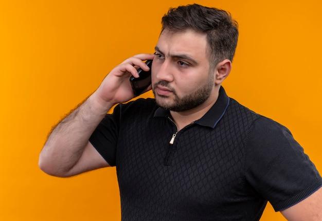 Młody brodaty mężczyzna w czarnej koszuli wygląda na zdezorientowanego i bardzo niespokojnego podczas rozmowy przez telefon komórkowy