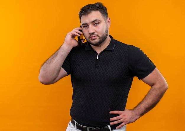 Młody brodaty mężczyzna w czarnej koszuli wygląda niezadowolony podczas rozmowy przez telefon komórkowy