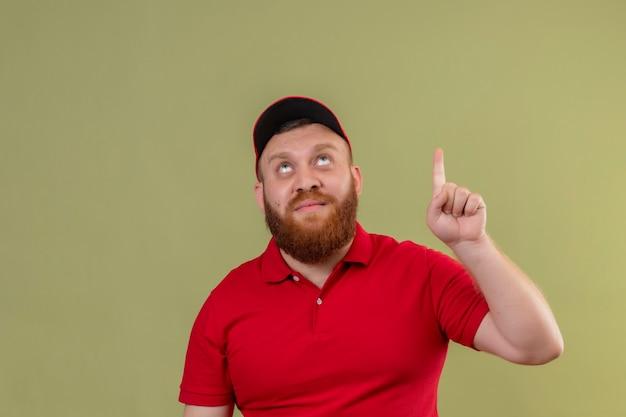 Młody brodaty mężczyzna w czerwonym mundurze i czapce patrząc w górę, wskazując palcem wskazującym, mając świetny pomysł