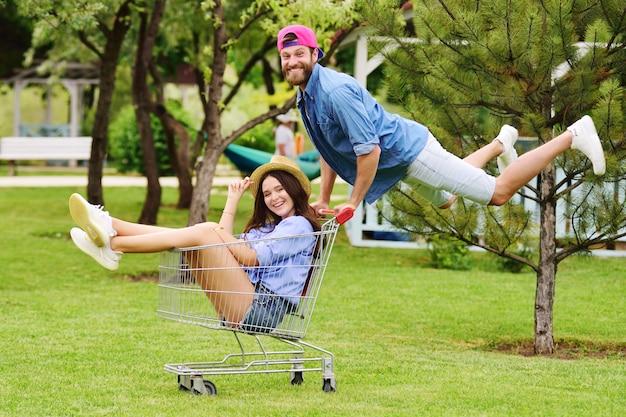 Młody brodaty mężczyzna w dżinsowej koszuli i różowej czapce prowadzi młodą, ładną, uśmiechniętą kobietę w słomkowym kapeluszu w supermarkecie na tle zieleni i parku.