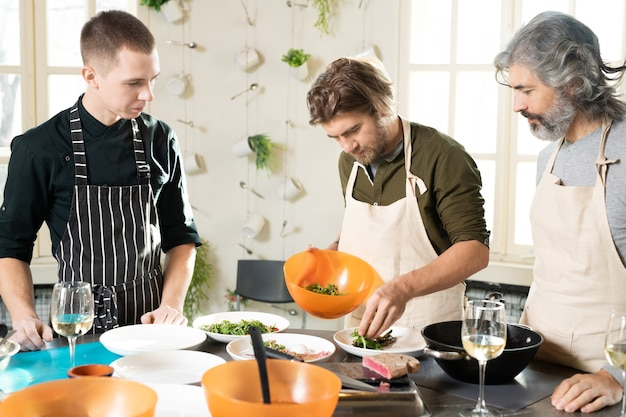 Młody brodaty mężczyzna w fartuchu pochyla się nad dużym stołem kuchennym i kładzie świeżą rukolę na talerzach wśród dojrzałego ucznia i trenera gotowania