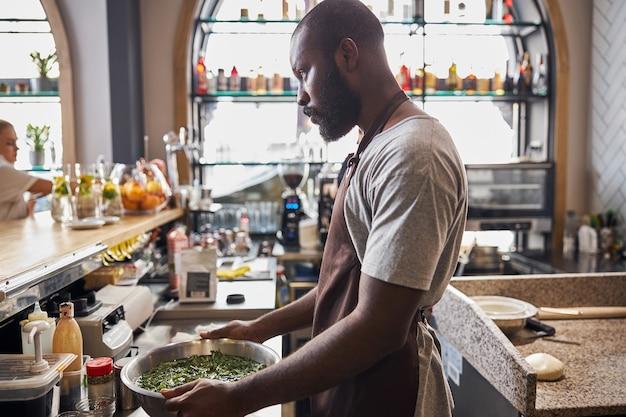 Młody brodaty mężczyzna w fartuchu stoi za barem w restauracji i myje zieleń na sałatkę