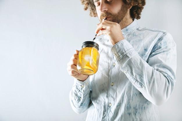 Młody brodaty mężczyzna w jasnej dżinsowej koszuli pije świeżą, domowej roboty pomarańczową cytrusową musującą lemoniadę przez pasiastą słomkę z rustykalnego przezroczystego słoika w rękach