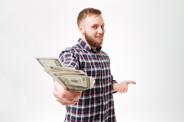 Młody brodaty mężczyzna w koszula pokazuje pieniądze
