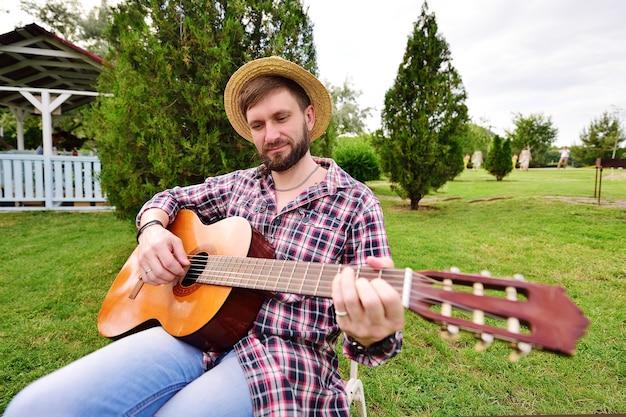 Młody brodaty mężczyzna w kraciastej koszuli i słomkowym kapeluszu gra na gitarze i uśmiecha się siedząc na krześle na tle parku, zielonej trawy i altany. rekreacja na świeżym powietrzu, weekend