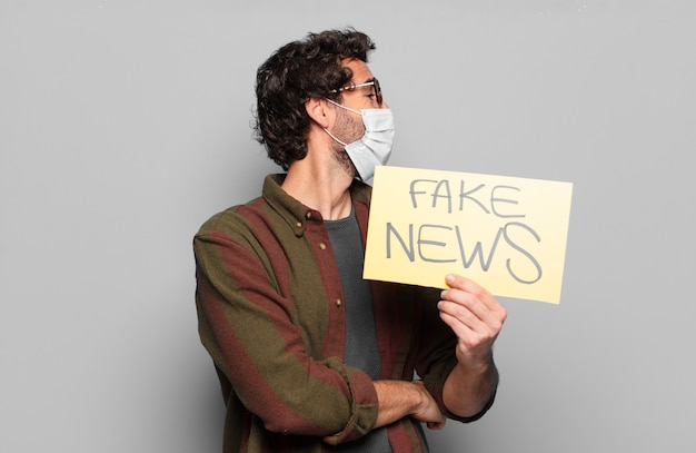 Młody brodaty mężczyzna w masce medycznej i fake news