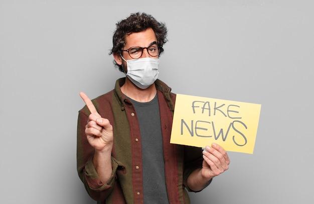 Młody brodaty mężczyzna w masce medycznej i fałszywej tablicy informacyjnej