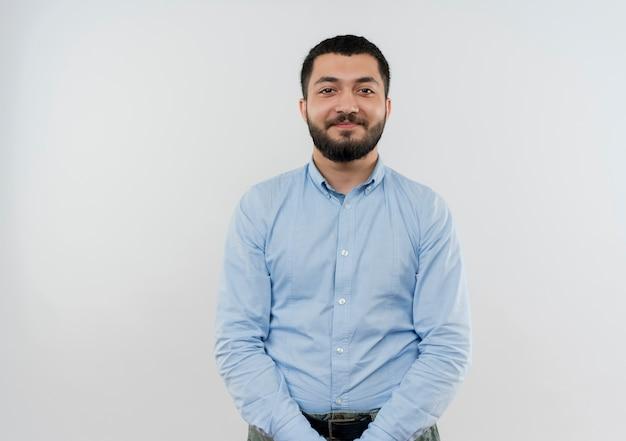 Młody brodaty mężczyzna w niebieskiej koszuli patrząc z przodu uśmiechając się pewnie stojąc na białej ścianie