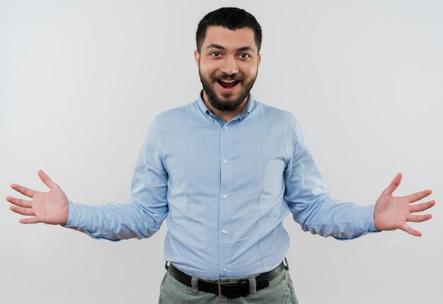 Młody brodaty mężczyzna w niebieskiej koszuli robi powitalny gest rękami uśmiechając się radośnie