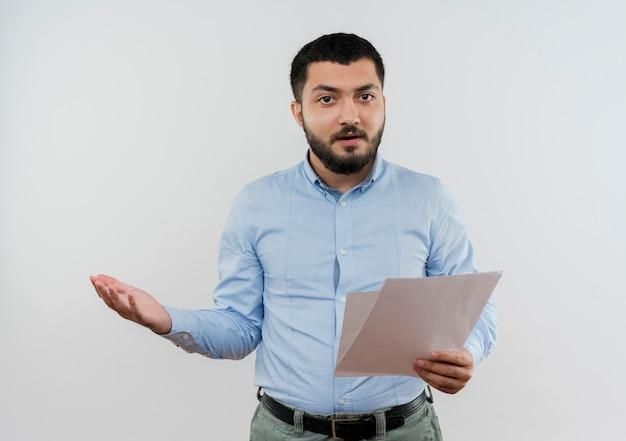Młody brodaty mężczyzna w niebieskiej koszuli trzyma puste strony patrząc z przodu z wyciągniętą ręką niezadowolony stojąc nad białą ścianą