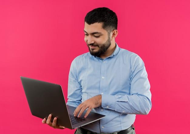 Młody brodaty mężczyzna w niebieskiej koszuli trzymając laptop pracuje nad nim z uśmiechem na twarzy