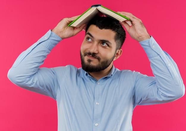 Młody brodaty mężczyzna w niebieskiej koszuli, trzymając otwartą książkę nad głową szmata, patrząc na bok z uśmiechem na twarzy