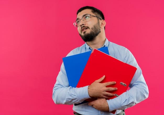Młody brodaty mężczyzna w okularach i niebieskiej koszuli, trzymając foldery patrząc zmęczony i przepracowany