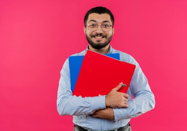 Młody brodaty mężczyzna w okularach i niebieskiej koszuli, trzymając foldery uśmiechnięty radośnie
