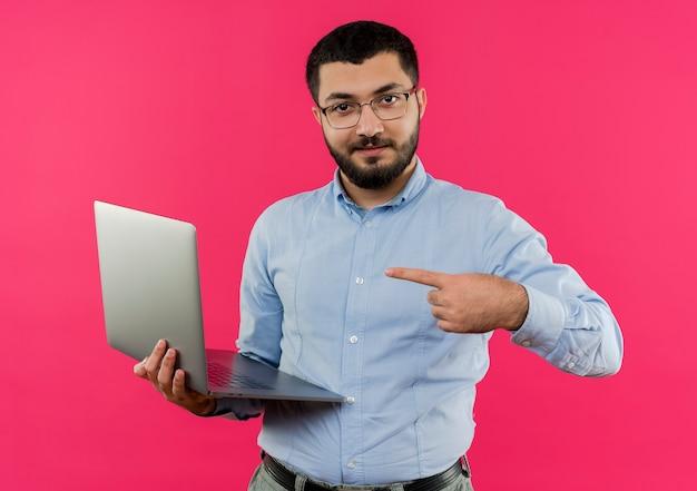 Młody brodaty mężczyzna w okularach i niebieskiej koszuli trzymając laptopa wskazać palcem wskazującym na to uśmiechnięty pewnie