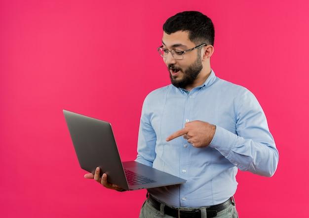 Młody brodaty mężczyzna w okularach i niebieskiej koszuli trzymając laptopa wskazując palcem na to jest zaskoczony