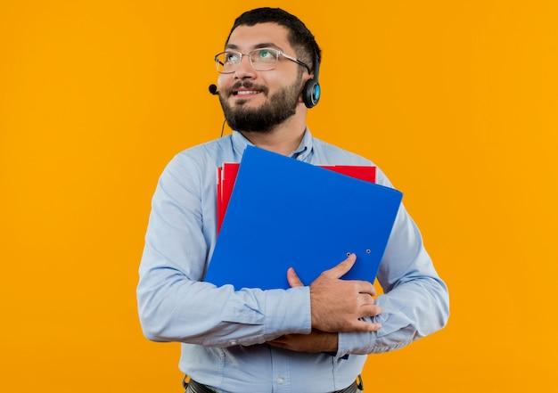Młody brodaty mężczyzna w okularach i niebieskiej koszuli ze słuchawkami z mikrofonem, trzymając foldery patrząc na bok z uśmiechem na twarzy