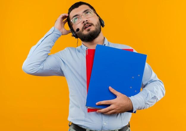 Młody brodaty mężczyzna w okularach i niebieskiej koszuli ze słuchawkami z mikrofonem, trzymając foldery patrząc zdziwiony