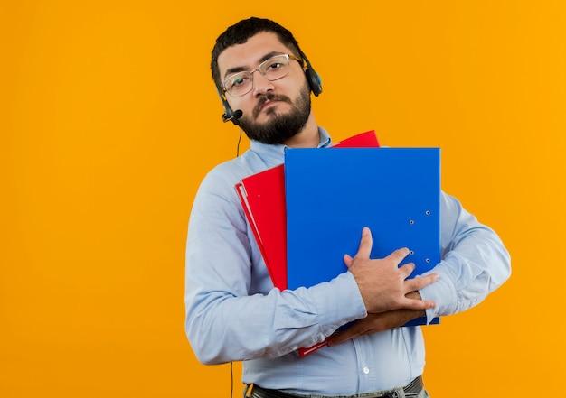 Młody brodaty mężczyzna w okularach i niebieskiej koszuli ze słuchawkami z mikrofonem, trzymając foldery z poważną miną