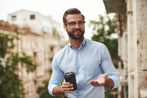 Młody brodaty mężczyzna w okularach i słuchawkach trzymający filiżankę kawy i rozmawiający z przyjacielem