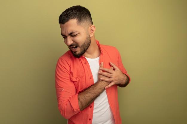 Młody brodaty mężczyzna w pomarańczowej koszuli, trzymając się za ręce na klatce piersiowej, czując ból stojąc nad jasną ścianą
