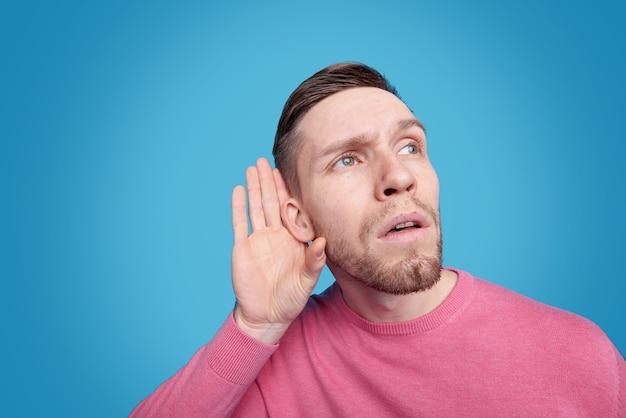 Młody brodaty mężczyzna w różowym swetrze trzymający rękę przy prawym uchu, podsłuchując lub próbując usłyszeć delikatny dźwięk