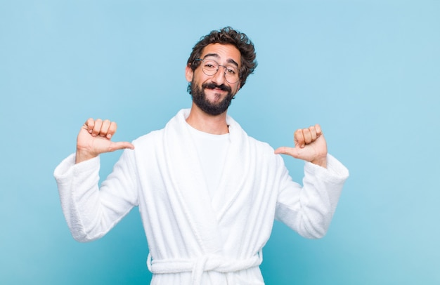 Młody brodaty mężczyzna w szlafroku czuje się dumny, arogancki i pewny siebie, wygląda na zadowolonego i odnoszącego sukcesy, wskazuje na siebie