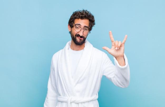 Młody brodaty mężczyzna w szlafroku czuje się szczęśliwy, zabawny, pewny siebie, pozytywny i zbuntowany, robi ręką znak rocka lub heavy metal