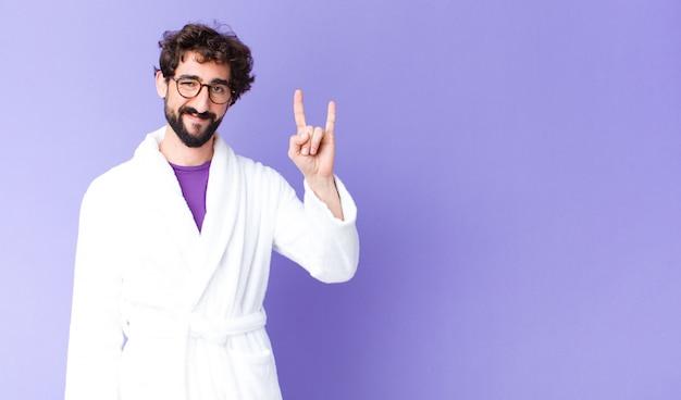 Młody brodaty mężczyzna w szlafroku czuje się szczęśliwy, zabawny, pewny siebie, pozytywny i zbuntowany, robiąc ręką znak rocka lub heavy metalu