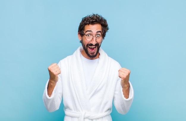 Młody brodaty mężczyzna w szlafroku czuje się szczęśliwy