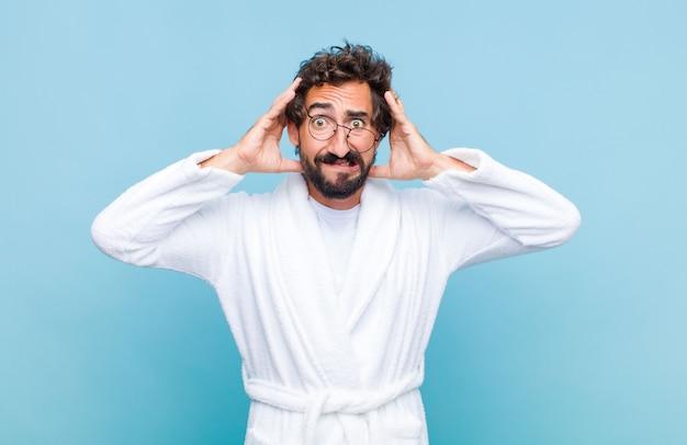 Młody brodaty mężczyzna w szlafroku czuje się zestresowany, zmartwiony, zaniepokojony lub przestraszony, z rękami na głowie, panikuje podczas pomyłki