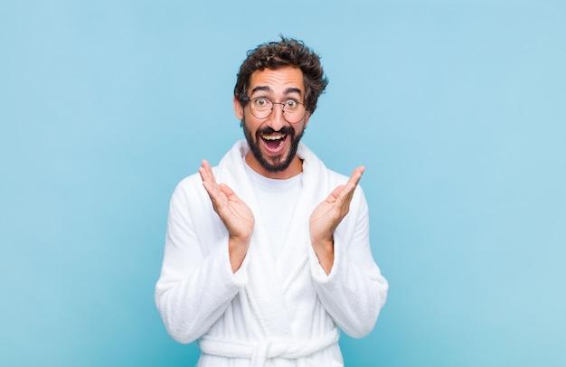 Młody brodaty mężczyzna w szlafroku czuje się zszokowany i podekscytowany, śmieje się, zdumiony i szczęśliwy z powodu niespodziewanej niespodzianki