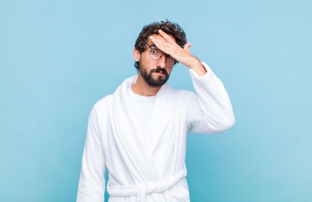 Młody brodaty mężczyzna w szlafroku panikuje z powodu zapomnianego terminu, czuje się zestresowany, musi zatuszować bałagan lub błąd
