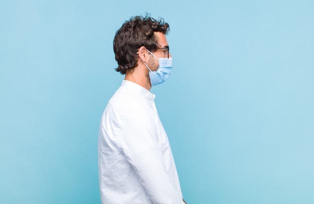 Młody brodaty mężczyzna w widoku profilu chce skopiować przestrzeń do przodu, myśleć, wyobrażać sobie lub marzyć