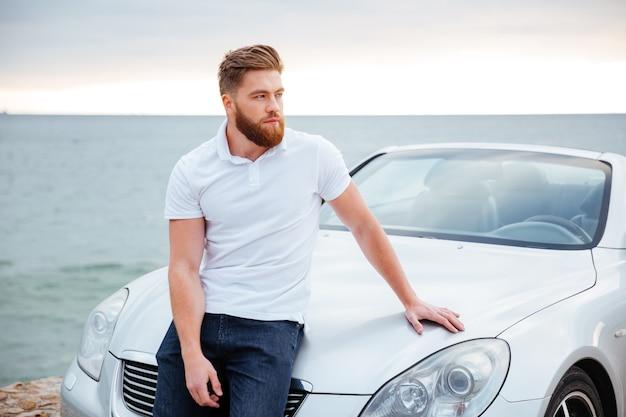 Młody brodaty mężczyzna wsparty na swoim samochodzie zaparkowanym na plaży