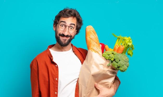 Młody brodaty mężczyzna wyglądający na szczęśliwego i mile zaskoczonego, podekscytowany z zafascynowanym i zszokowanym wyrazem twarzy, trzymający torebkę z warzywami